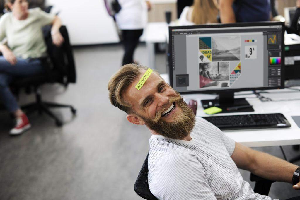 Ein Mann sitzt lachend im Büro