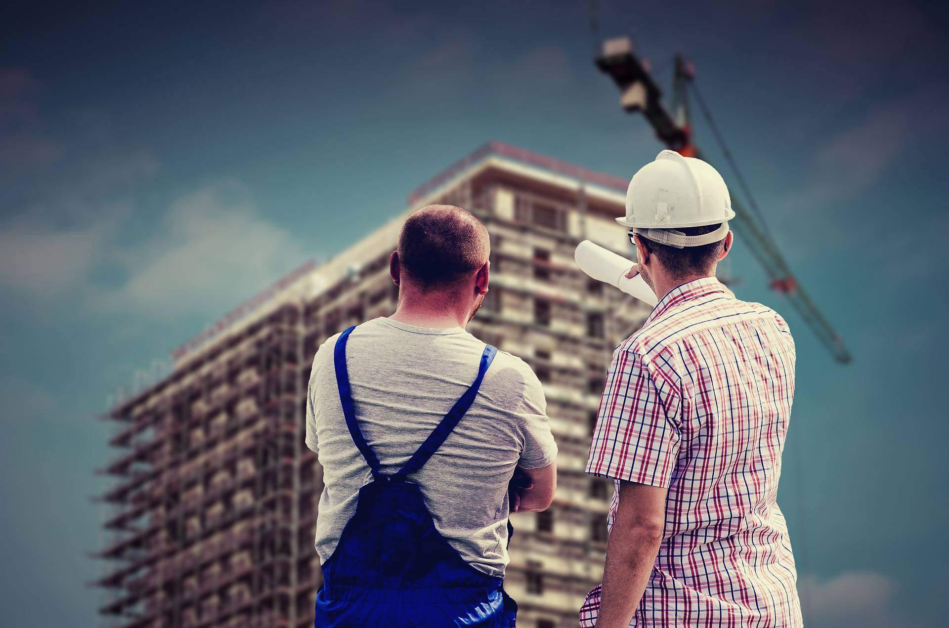 Zwei Bauarbeiter beobachten ein Gebäude, das gerade gebaut wird