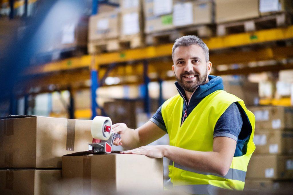 Lächelnder Logistikarbeiter mit Paketen