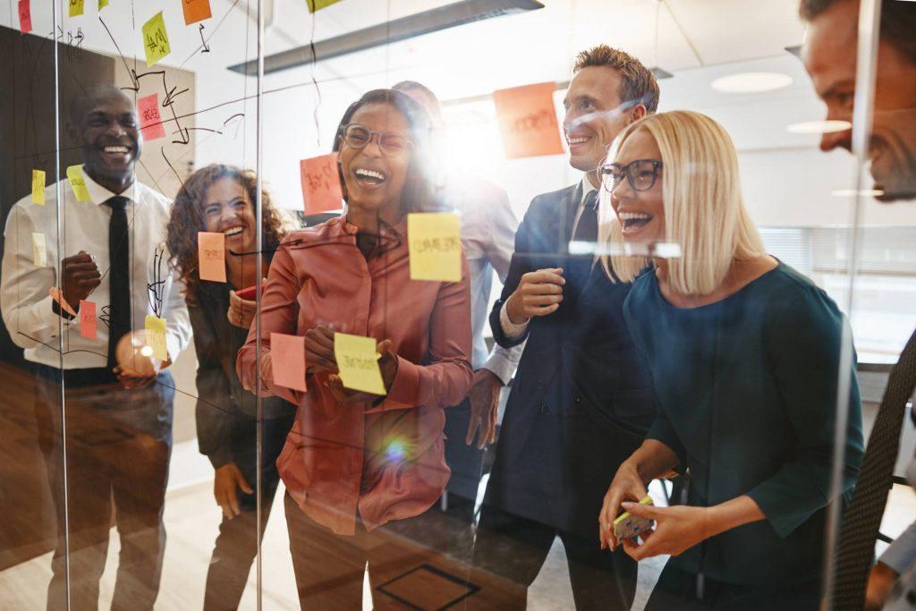 Eine Gruppe lachender Menschen in einem Büro während eines Brainstormings